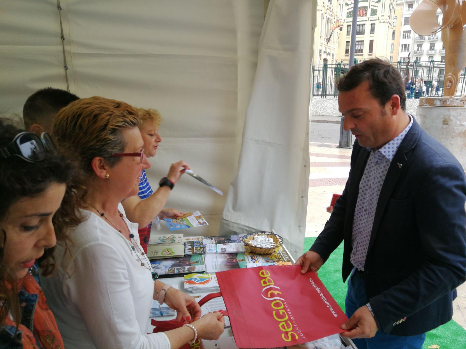 Una profesional de la Oficina de Turismo de Segorbe entrega información sobre la ciudad